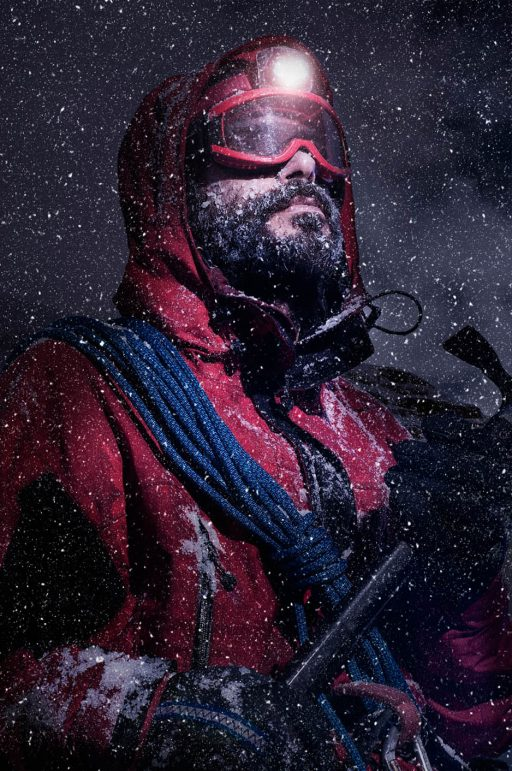 Portrait of a mountaineer during a heavy snowfall. Equipped with front light and ax