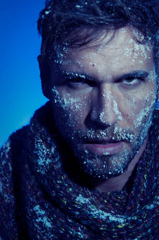 conceptual portrait of a man with his face frozen with snow